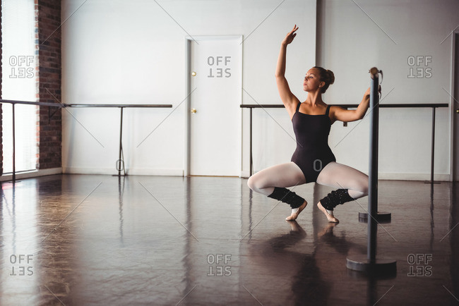 Ballerina practicing ballet moves at barre in ballet studio