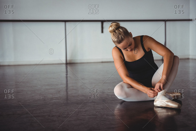 Ballerina adjusting stockings while sitting in ballet studio