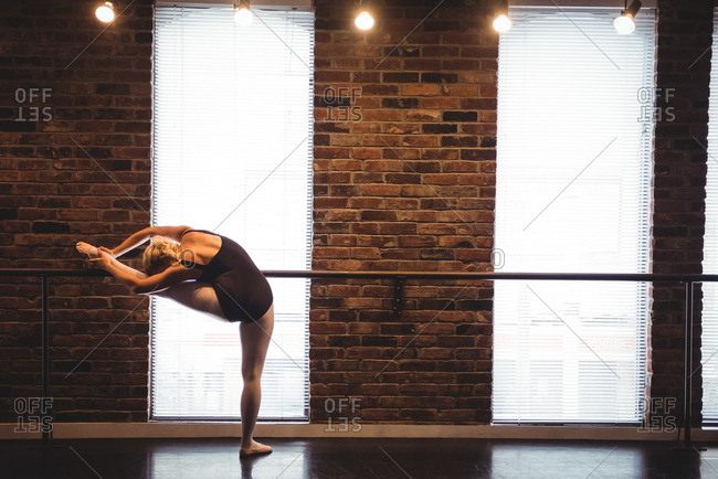 Ballerina stretching at barre in ballet studio