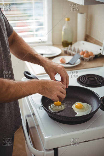 Mid section of man cracking an egg into a frying pan in the kitchen at home