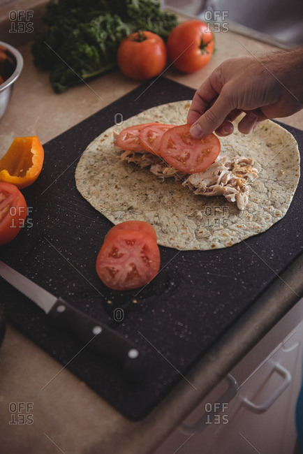 Close-up of man hands placing tomato slices on the burrito in kitchen at home