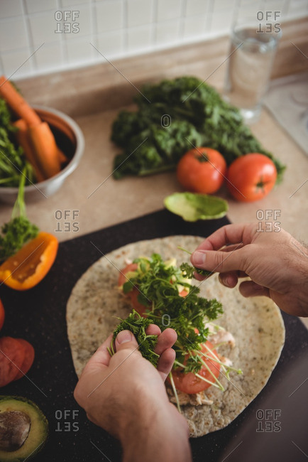 Close-up of mans hand placing herbs on burrito on kitchen worktop