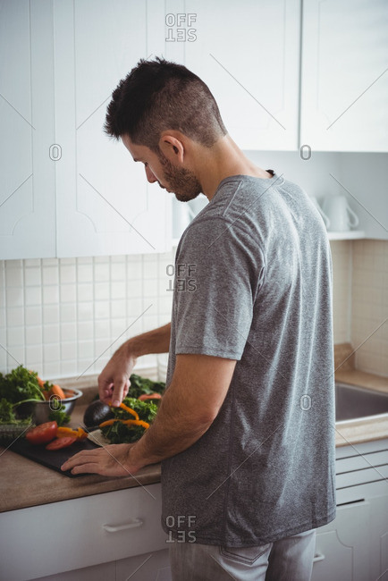 Rear view of man placing a bell pepper on burrito in the kitchen at home