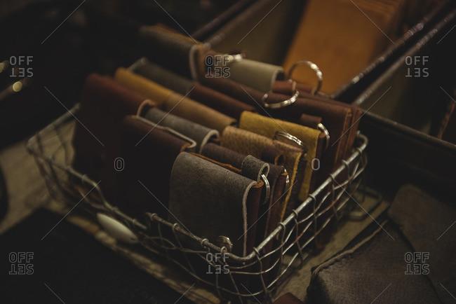 Various leather wallet in steel crate in workshop