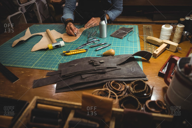 Mid-section of craftswoman working on a piece of leather in workshop