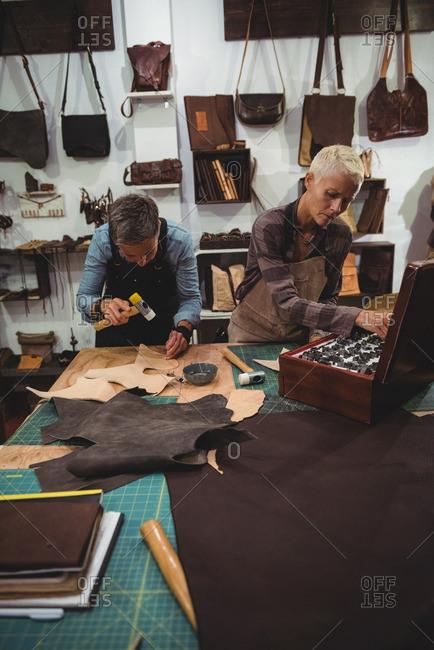 Attentive craftswoman hammering leather in workshop