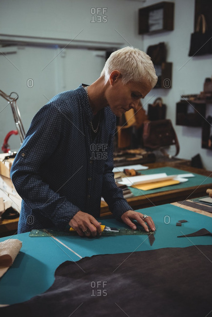 Attentive craftswoman working on a piece of leather in workshop