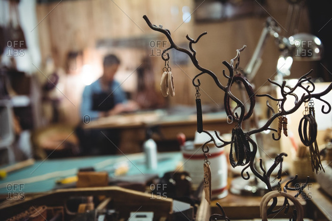 Various leather accessories hanging on hook in workshop