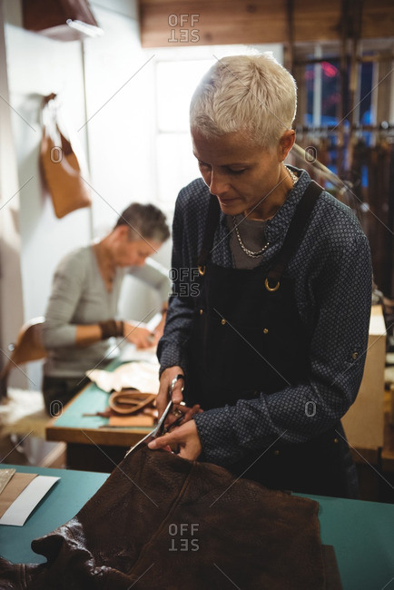 Attentive craftswoman cutting leather in workshop