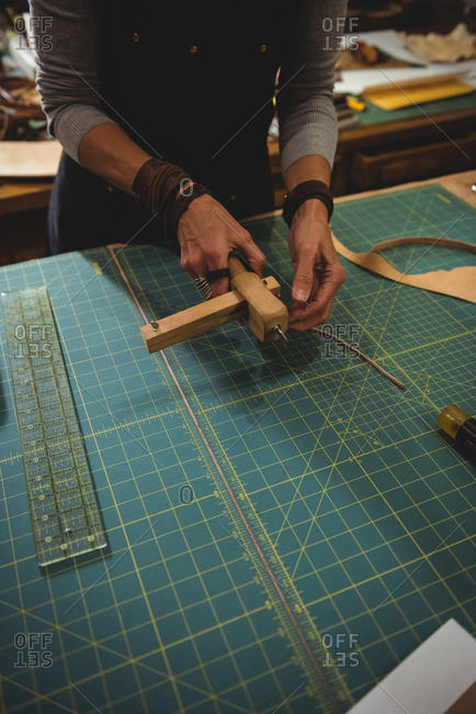 Mid-section of craftswoman preparing leather belt