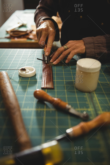 Mid-section of craftswoman cutting leather in workshop