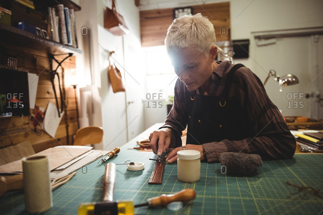 Attentive craftswoman cutting a piece of leather in workshop