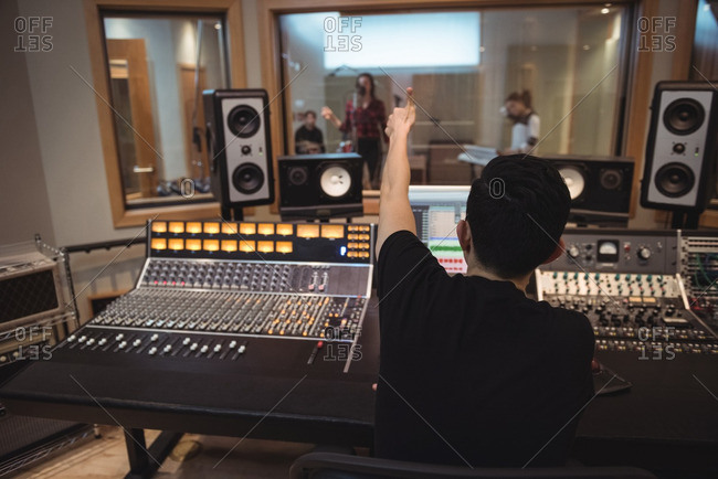 Audio engineer signaling to musicians while recording in studio