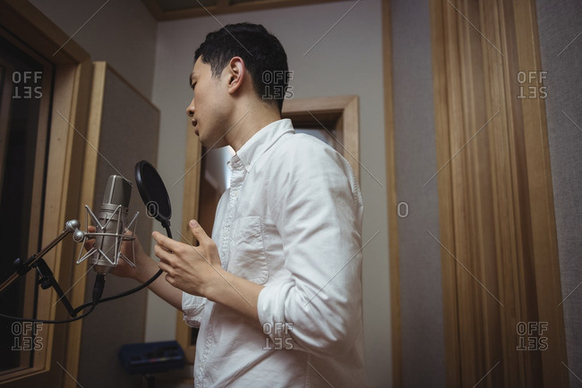 Man singing on microphone in recording studio