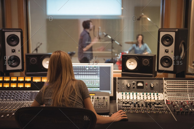 Rear view of audio engineer using sound mixer in recording studio