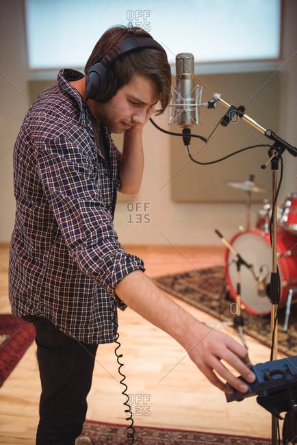 Man adjusting volume while singing in music studio