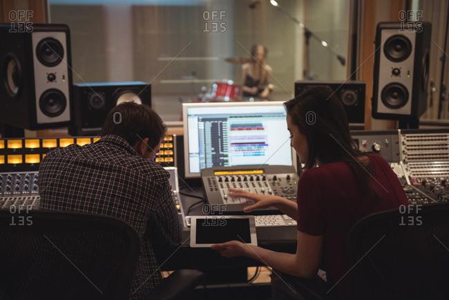 Audio engineers using digital tablet while sitting in recording studio