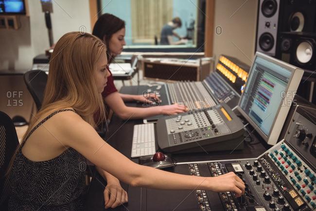Audio engineers using sound mixer in recording studio