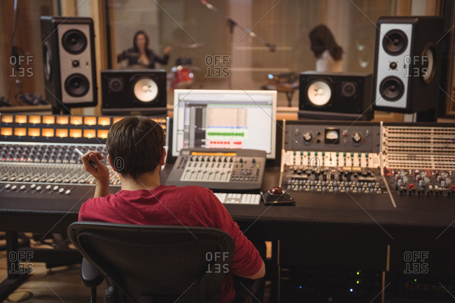 Audio engineer working on sound mixer in recording studio