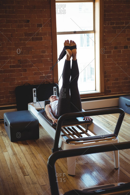 Woman practicing pilates on reformer in fitness studio