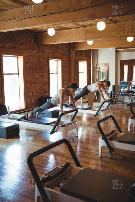 Women practicing pilates on reformer in fitness studio