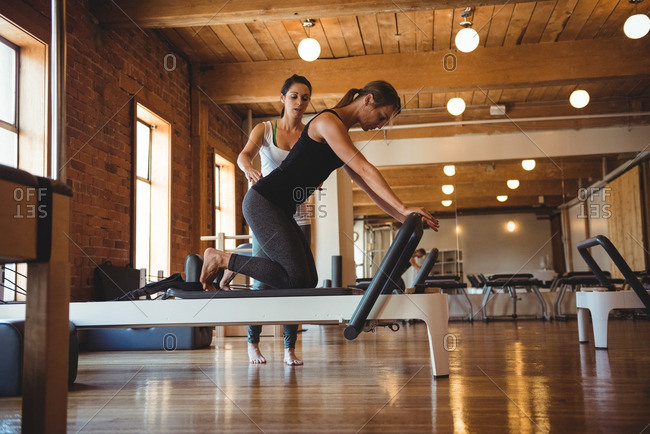 Trainer helping a woman while practicing pilates in fitness studio