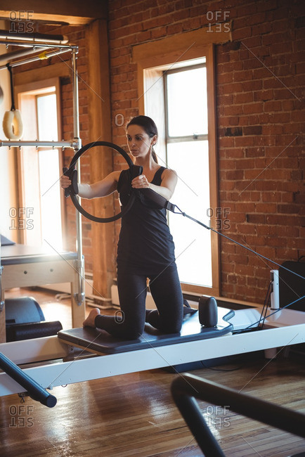 Woman practicing pilates on reformer using exercise ring in fitness studio