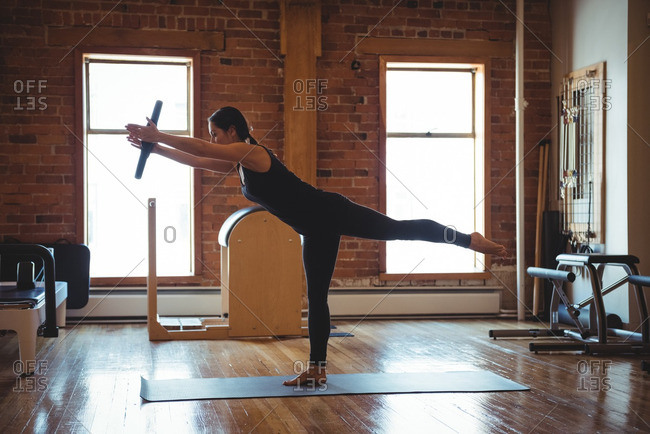 Woman practicing on pilates while standing on one leg in fitness studio
