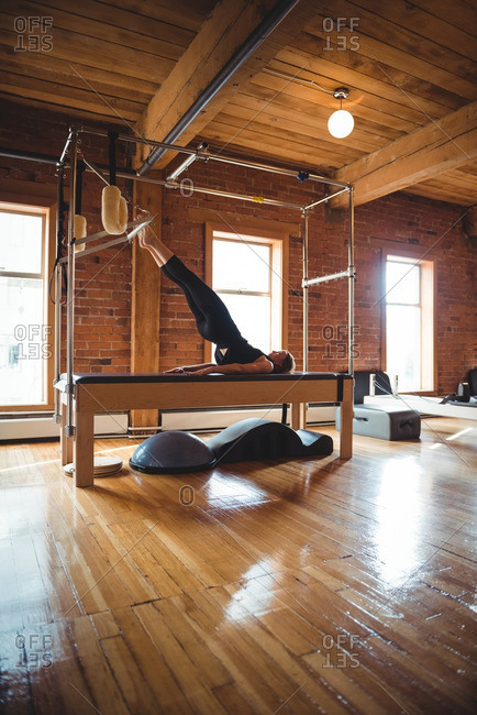 Determined woman practicing pilates in fitness studio