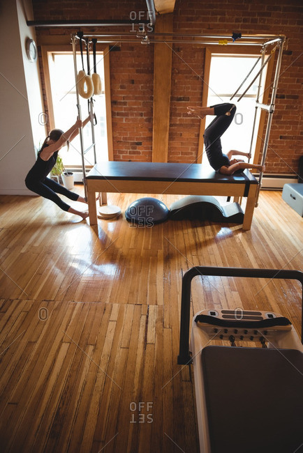Determined women practicing pilates in fitness studio