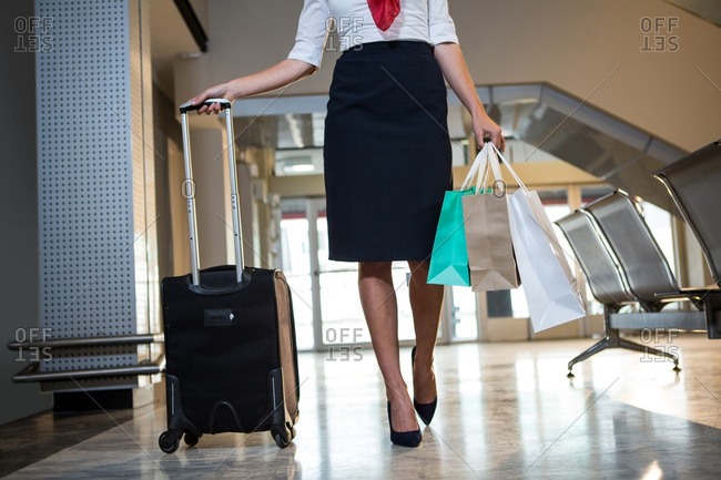 Airhostess walking with trolley bag and shopping bags at airport terminal