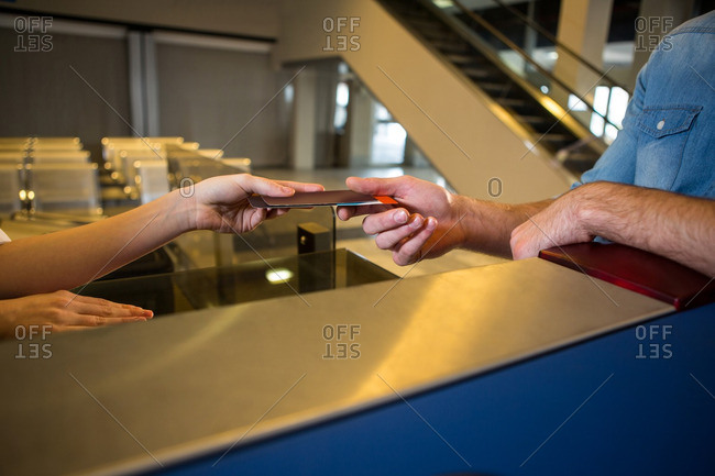 Close-up of female staff giving boarding pass at the check in desk