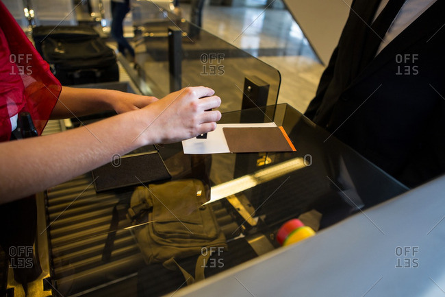 Mid section of female staff putting a stamp on boarding pass