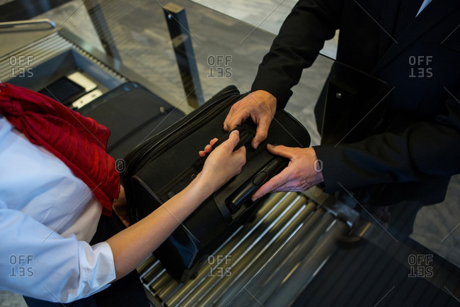 Mid section of female staff handing over luggage to businessman