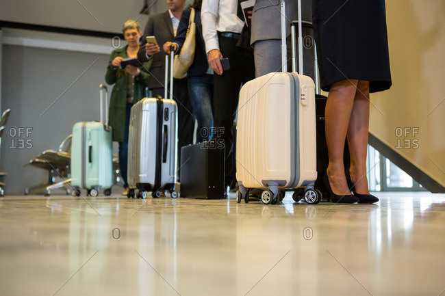 Low section of passengers with trolley bag standing in a queue