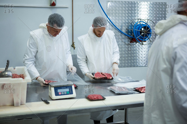 Butchers weighing packages of meat at meat factory