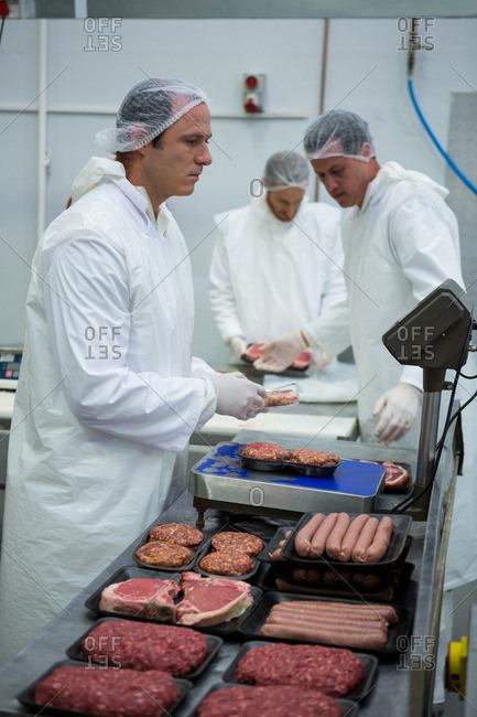 Butchers weighing packages of minced meat at meat factory