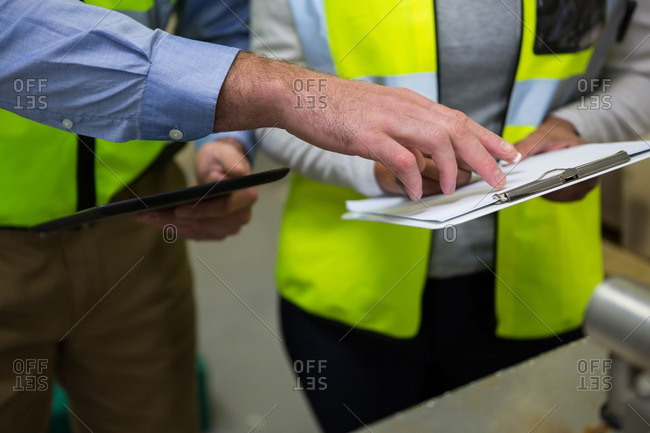 Close-up of technicians discussion over clipboard