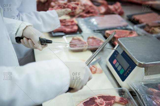 Butcher sharpening his knife at meat factory
