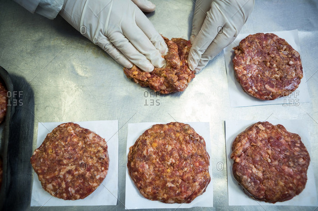 Close-up of butcher packaging hamburger patty at meat factory