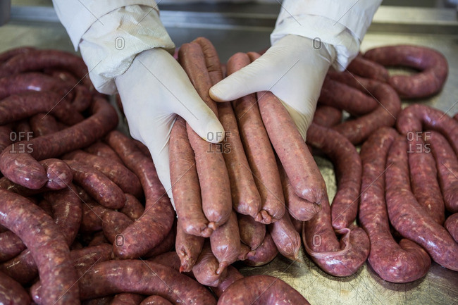 Close-up of butcher holding sausages at meat factory