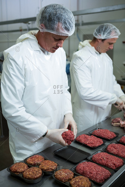Butcher arranging minced meat in packaging tray in meat factory