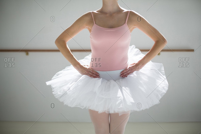 Mid section of ballerina practicing a ballet dance in ballet studio