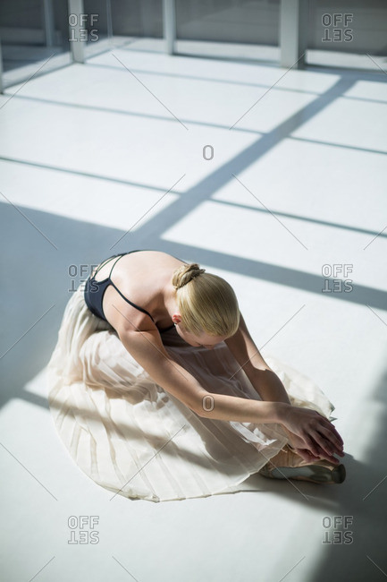 Ballerina doing stretching exercise in the ballet studio