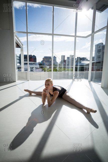 Ballerina stretching on the floor at studio