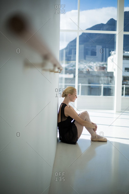Depressed ballerina sitting against wall in the studio