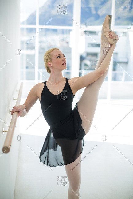 Ballerina stretching on a barre while practicing ballet dance in the studio