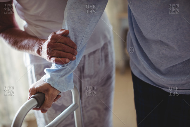 Senior woman helping senior man to walk with walker at home