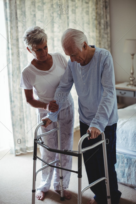Mid section of senior woman helping senior man to walk with walker at home