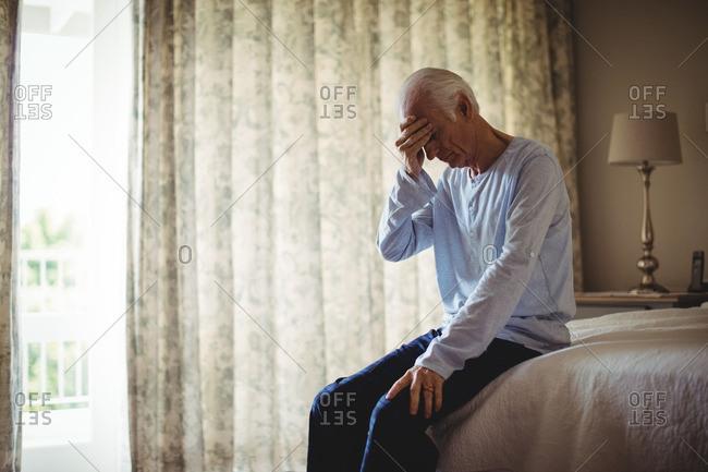 Worried senior man in bedroom at home